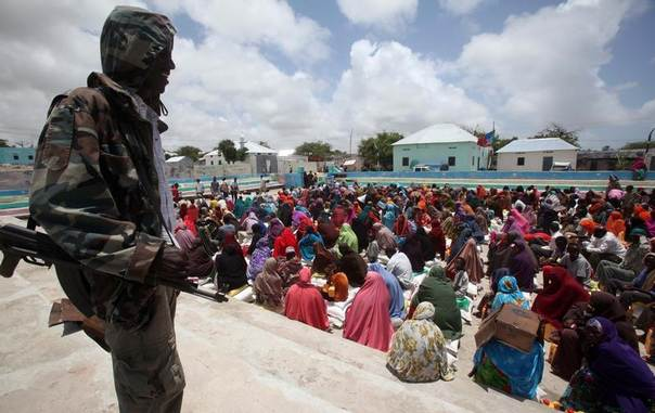 A Somali government soldier keeps watch over internally displaced people as they wait for food aid at a centre in Ubeyd camp in Mogadishu. Somalia, September 17, 2012. REUTERS/Ismail Taxta