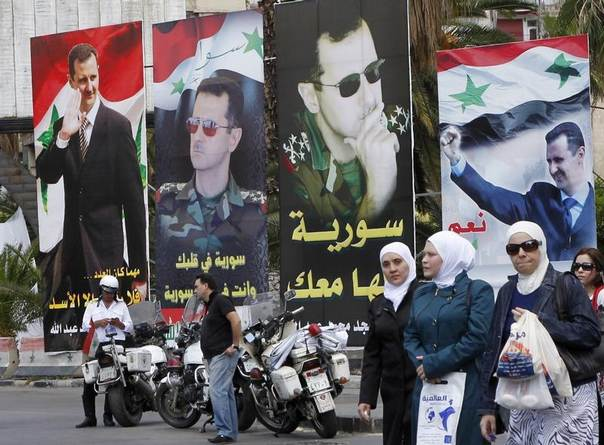 Women walk past election posters of Syria's President Bashar al-Assad along a street in Damascus, Syria, June 2, 2014. REUTERS/Khaled al-Hariri