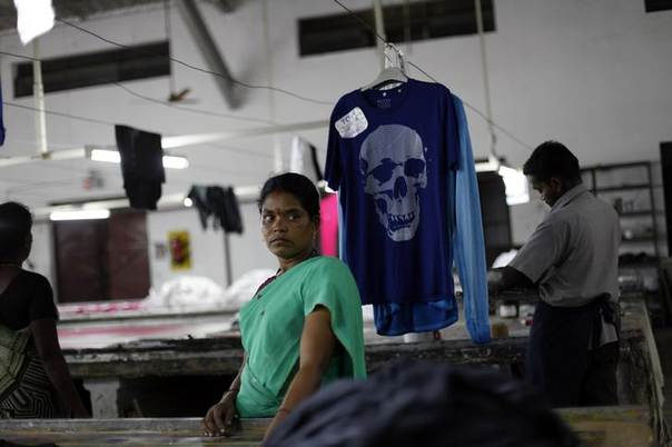 An employee stands next to a newly dyed T-shirt at the Estee garment factory in Tirupur, in the southern Indian state of Tamil Nadu June 19, 2013. REUTERS/Mansi Thapliyal
