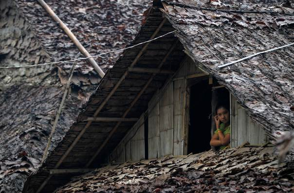 A Burmese refugee watches from her bamboo-and-leaf thatch house as Thai authorities conduct a census at Mae La refugee camp, near the Thailand-Myanmar border in Mae Sot district, Tak province, on July 21, 2014. Thai authorities have started conducting the census at Mae La on refugees who fled neighbouring Myanmar, in a bid to crackdown on illegal workers, but raising fears among the refugees of an imminent repatriation to Myanmar. REUTERS/Chaiwat Subprasom