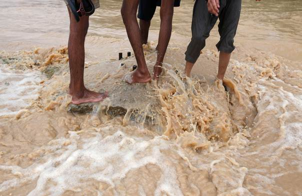 Barefooted men take break on a road median while wading through flood waters on the outskirts of Karachi, Pakistan, on August 4, 2013. REUTERS/Akhtar Soomro