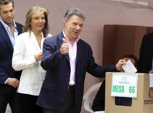 President Juan Manuel Santos gestures before casting his vote as he is accompanied by his wife Maria Clemencia and son Martin in Bogota June 15, 2014 REUTERS/Jaime Saldarriaga