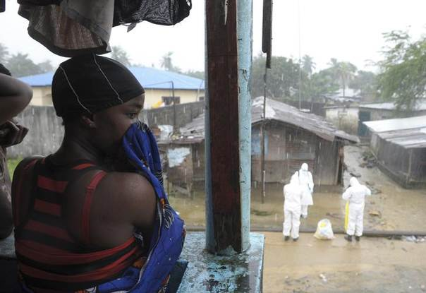 A Liberian woman stands as health workers wearing protective clothing prepare to carry an abandoned dead body presenting Ebola symptoms at Duwala market in Monrovia August 17, 2014. REUTERS/2Tango