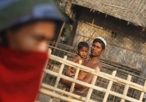 A Rohingya man carrying his child looks at police and volunteer conducting a national census at a Rohingya village in Sittwe, the capital of Rakhine State, Myanmar, April 1, 2014. TREUTERS/Soe Zeya Tun