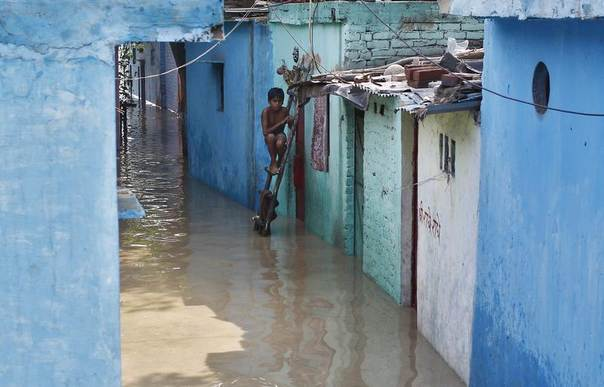 A boy sits on a ladder next to his flooded house in New Delhi. Water levels have risen on the river Yamuna after heavy monsoon rains June 19, 2013. REUTERS/Anindito Mukherjee