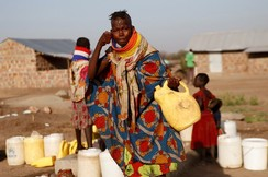 A Turkana woman washes her face at a water point within Kalobeyei Settlement outside the Kakuma refugee camp in Turkana county