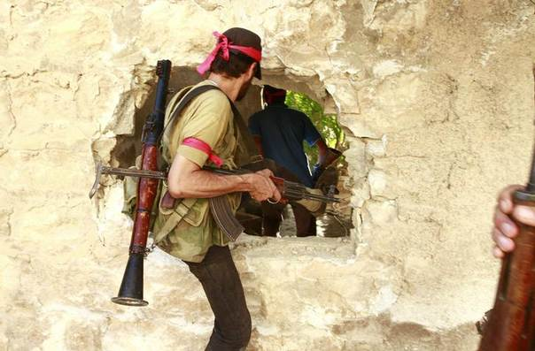 Free Syrian Army fighters move through a hole in a wall in the northern town of Khan al-Assal, after seizing it July 22, 2013. REUTERS/Hamid Khatib