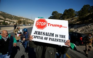 Palestinian demonstrator holds placard during a protest against a promise by U.S. President-elect Donald Trump to re-locate U.S. embassy to Jerusalem, in the West Bank near Jewish settlement of Maale Adumim