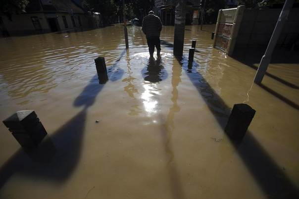 A man walks through flood waters in the town of Obrenovac, southwest of Belgrade, Serbia, May 19, 2014. REUTERS/Antonio Bronic