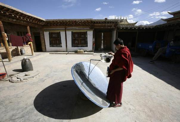 A Tibetan monk makes lunch with a simple solar energy stove at Longwu monastery in Tongren, Qinghai province, China, Oct. 22, 2009. REUTERS/Jason Lee
