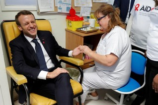 A nurse takes blood for a HIV test for French President Emmanuel Macron as he visits the Delafontaine Hospital in Saint-Denis, Freance as part of the World AIDS Day