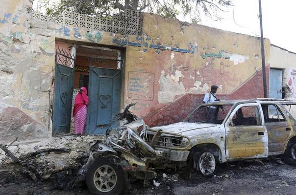 A woman and a policeman look at the scene of a car bomb attack near the Oriental Hotel in Somalia's capital Mogadishu, February 10, 2014. REUTERS/Feisal Omar
