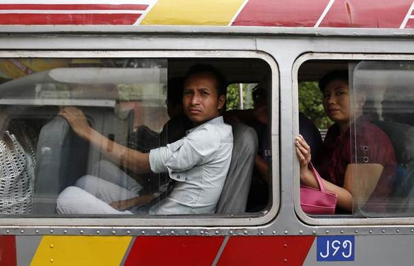 Passengers look out the windows of a bus as they travel around Yangon, July 3, 2013.  REUTERS/Soe Zeya Tun
