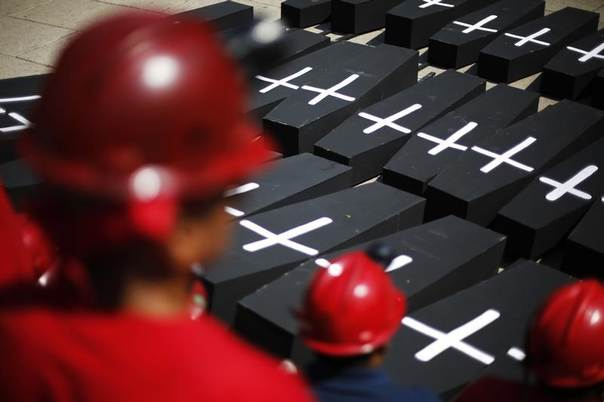 Miners stand near mock coffins during a protest in commemoration of the 2006 mine blast in Mexico City, Feb. 19, 2014. REUTERS/Bernardo Montoya