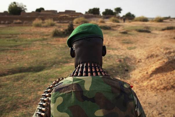 A Malian soldier wears a belt of ammunition around his neck before going to the village of Kadji in Gao, Mali, March 1, 2013. REUTERS/Joe Penney
