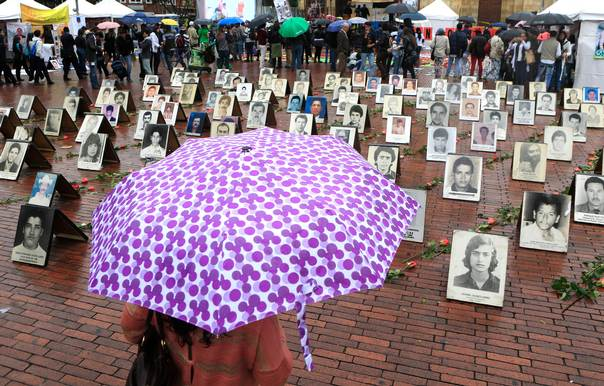 A woman holding an umbrella looks at portraits of missing people during an event for International Week of the Disappeared, in Bogota, on May 27, 2014. REUTERS/Jose Miguel Gomez