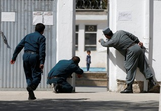 Policemen try to rescue a child at the site of a suicide attack on a Shi'ite Muslim mosque in Kabul