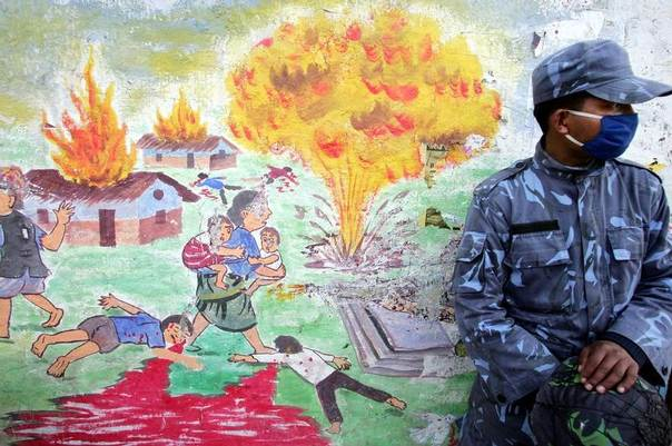 In this 2005 file photo a policeman stands guard in front of a wall containing graffiti at a street in Kathmandu, Nepal. REUTERS/Arko Datta