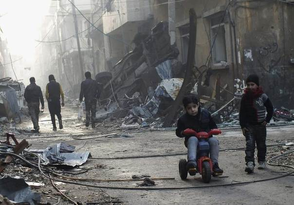 A boy rides on a tricycle along a damaged street in the besieged area of Homs, January 1, 2014. REUTERS/Yazan Homsy