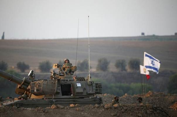 n Israeli soldier sits atop a mobile artillery unit near the border with Gaza, July 23, 2014. REUTERS/Ronen Zvulun