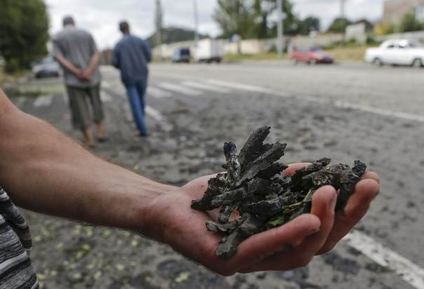 A man shows pieces of shrapnel collected after what locals say, was recent shelling by Ukrainian forces in Donetsk, Ukraine, August 23, 2014. REUTERS/Maxim Shemetov