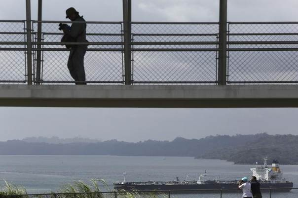 Visitor is seen as a cargo boat waits to enter the panama canal next to a construction site of the Expansion project (not pictured) on the outskirts of Colon City February 20, 2014.  REUTERS/Carlos Jasso