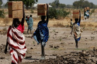 Women carry boxes of food aid delivered by the United Nations in Rubkuai village, South Sudan