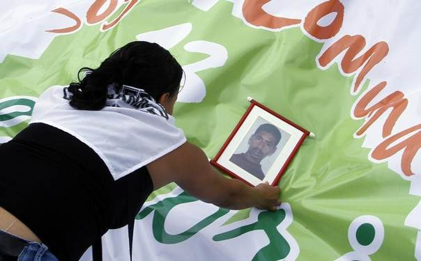A woman puts down a photograph of a family member who disappeared, at a memorial for people missing or killed in armed conflict, in Medellin, Colombia, April 9, 2012. REUTERS/Albeiro Lopera