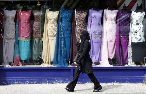 A woman walks past a clothes shop in the Sparkbrook area of Birmingham, central England May 12, 2011. REUTERS/Darren Staples