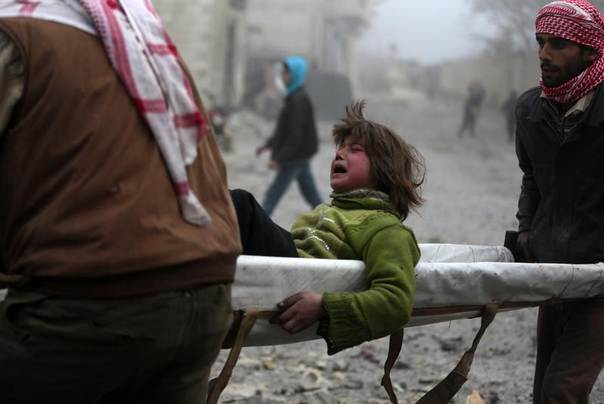 A boy reacts as he is carried on a stretcher at a damaged site after what activists said was heavy shelling by forces loyal to Syrian President Bashar Al-Assad in Duma, Damascus, Syria, December 26, 2013. REUTERS/Bassam Khabieh
