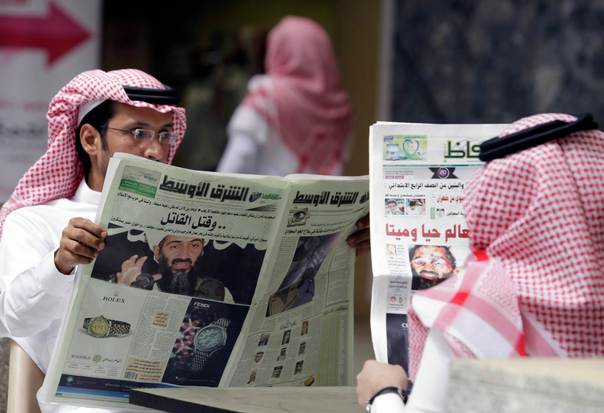 People read the newspapers with cover stories about Osama bin Laden, in Riyadh, May 3, 2011. Bin Laden was killed in a U.S. special forces assault on a Pakistani compound, then quickly buried at sea. REUTERS/Mohammed Mashhor