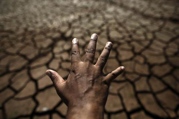 A man's hand is seen in front of the cracked ground of Jaguary dam during a long drought period that has hit the state of Sao Paulo in Braganca Paulista, 100 km from Sao Paulo, Brazil, Jan. 31, 2014. REUTERS/Nacho Doce