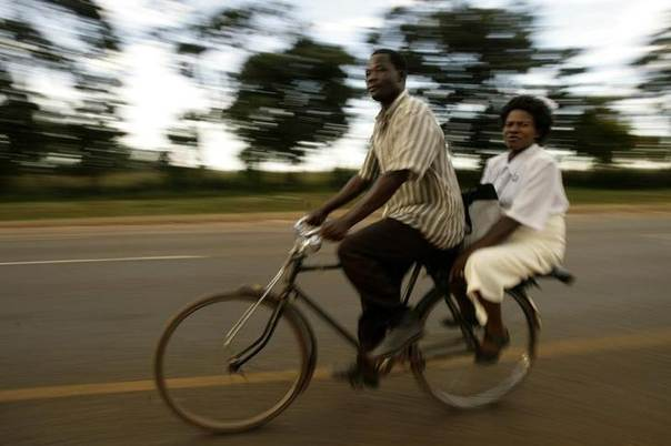 A nurse (R) returns from work on a bicycle along the Mchinji road-the highway linking Malawi to Zambia's eastern province, April 21, 2008. REUTERS/Siphiwe Sibeko