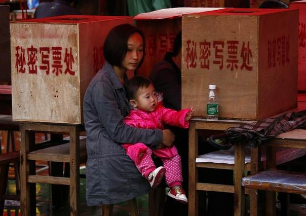 A woman holds her baby as her husband votes during an election for the next village chief and committee, amid heavy rainfalls in Wukan village, Guangdong province March 31, 2014REUTERS/Petar Kujundzic