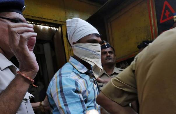Police escort one of the four men convicted of raping a photojournalist outside a jail in Mumbai March 21, 2014. The attack sparked street protests in the city and raised fresh questions about attitudes towards women in India. REUTERS/Mansi Thapliyal