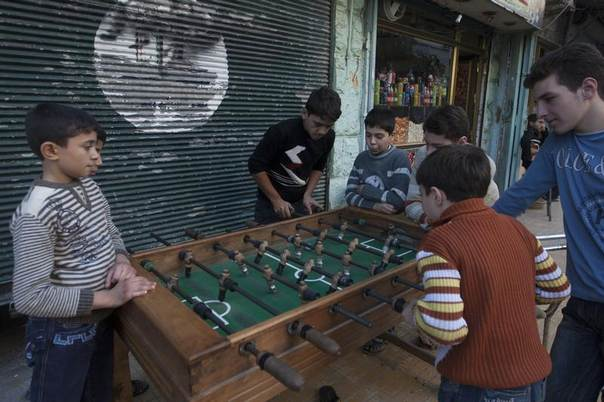 Children play a game of table football in Aleppo's al-Mashhad district, Syria, October 22, 2013. REUTERS/Mahmoud Hassano