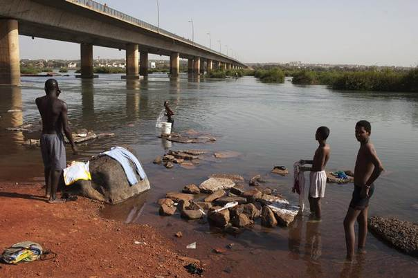 Boys wash clothes as a man washes himself in the Niger River in Bamako February 11, 2013. REUTERS/Joe Penney