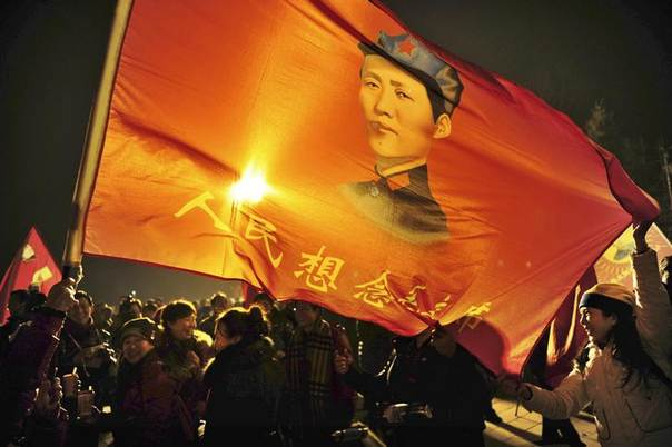 Supporters wave a flag bearing an image of the late Chairman Mao Zedong and a slogan which read