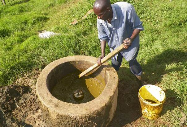 John Kipkoech stirs cow dung in a biodigester at a school in Kenya's Rift Valley. TRF/Caleb Kemboi