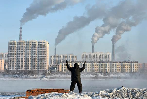 An elderly man exercises in the morning as he faces chimneys emitting smoke across the Songhua river in China's Jilin province, on February 24, 2013. REUTERS/Stringer