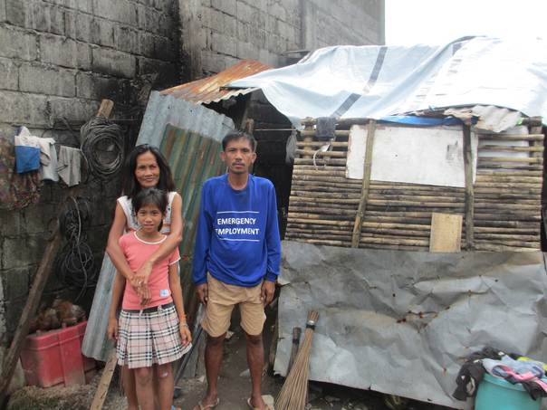 A Filipino family stands in front of a shelter patched together with wood and metal debris. Credit: Refugees International