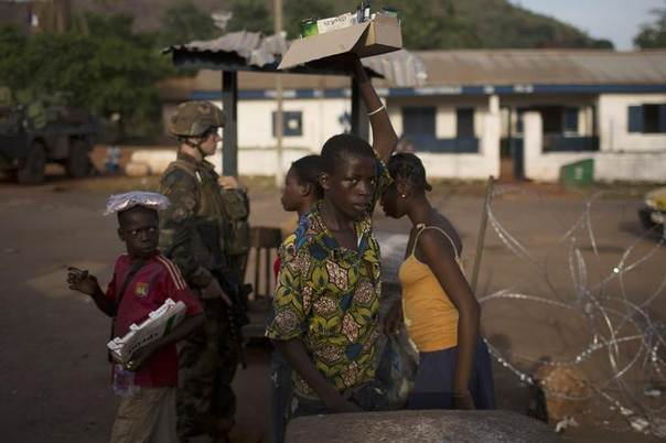 A street seller looks at the camera he walks through a security checkpoint manned by French peacekeeping soldiers and local gendamerie at Kilometre 12 (PK12) in the capital Bangui March 3, 2014. REUTERS/Siegfried Modola