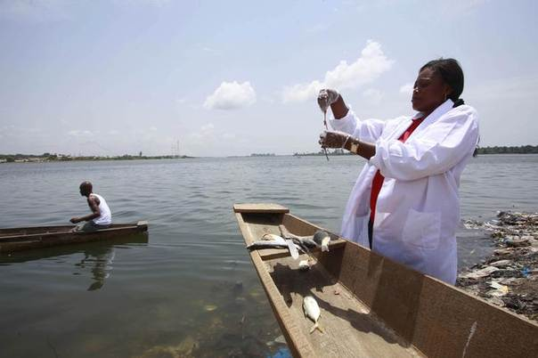 Dr Celine Nobah (R) of the Association of Women Researchers in the Ivory Coast stands beside a canoe as she conducts research to ensure that fish in the lagoon Ebrie are safe to eat, in Nbadon, Abidjan, on March 4, 2013. REUTERS/Thierry Gouegnon