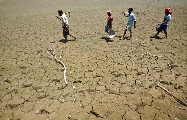 Labourers walk through a parched land of a dried lake on the outskirts of Agartala, capital of India's northeastern state of Tripura, on April 23, 2013. REUTERS/Jayanta Dey