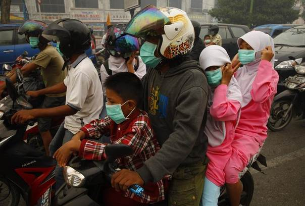 People wear face masks while waiting at a traffic junction in haze-hit Dumai, in Indonesia's Riau province, June 21, 2013. Hospitals in Dumai and Bengkalis in Indonesia's Riau province recorded increases in cases of asthma, lung, eye and skin problems due to smoke from plantation fires, said health official Arifin Zainal. REUTERS/Beawiharta