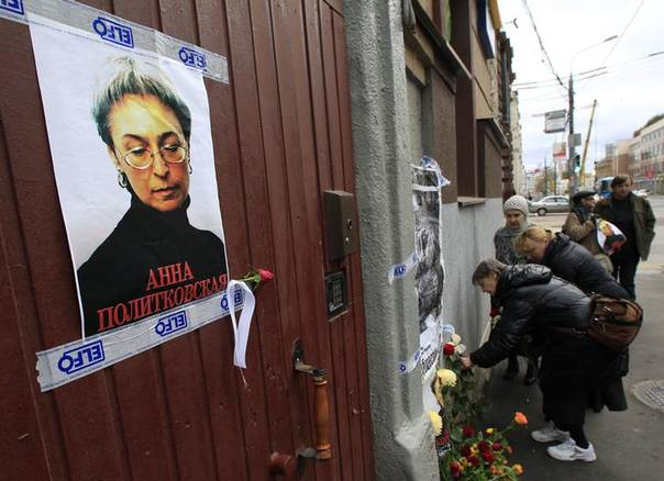 People lay flowers next to a portrait of slain journalist Anna Politkovskaya on the sixth anniversary of her death, at her block of flats in central Moscow October 7, 2012. REUTERS/Sergei Karpukhin
