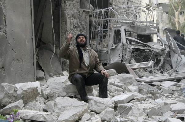 A man gestures while resting at a damaged site after what activists said was shelling by forces loyal to Syria's President Bashar al-Assad in Al-Sukkari neighbourhood in Aleppo February 2, 2014. REUTERS/Karam al halabi