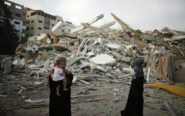 A Palestinian woman holding her daughter looks at the rubble of a residential tower, which witnesses said was destroyed in an Israeli air strike, in Gaza City August 24, 2014. REUTERS/Mohammed Salem