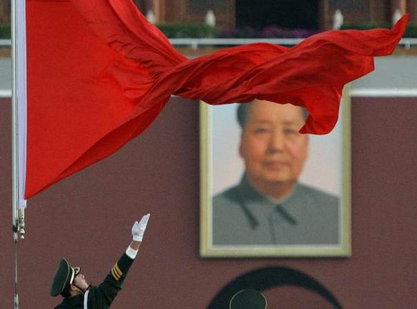 A soldier unfurls the Chinese national flag as it is raised in front of the giant portrait of Chairman Mao Zedong in Beijing's Tiananmen Square October 15, 2007. REUTERS/David Gray