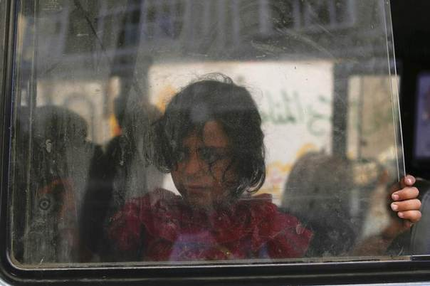 A girl looks through the window of a minibus as her family prepares to leave the Beit Hanoun neighbourhood in Gaza City August 8, 2014.  REUTERS/Siegfried Modola